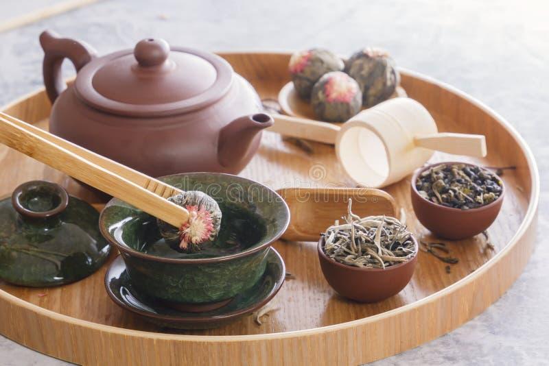 Le bourgeon du thé vert est plongé dans une tasse de porcelaine de chinois traditionnel avec les brucelles en bois spéciales image stock