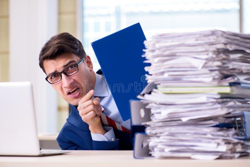Le bourreau de travail d'homme d'affaires luttant avec la pile des écritures photos stock