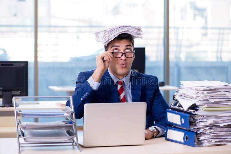Le bourreau de travail d'homme d'affaires luttant avec la pile des écritures images stock