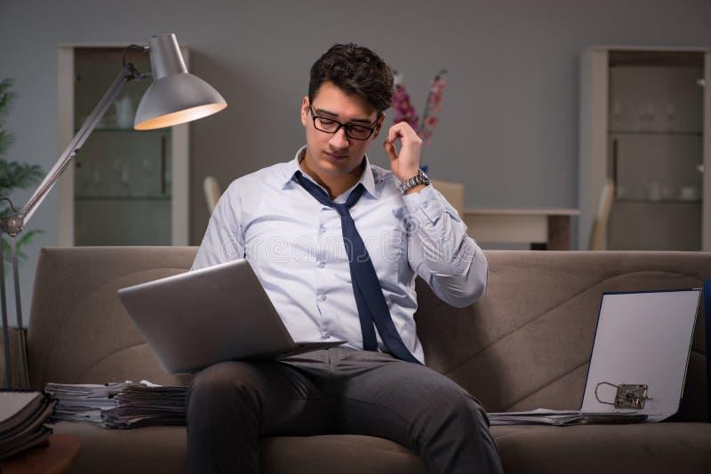 Le bourreau de travail d'homme d'affaires fonctionnant tard à la maison photos stock