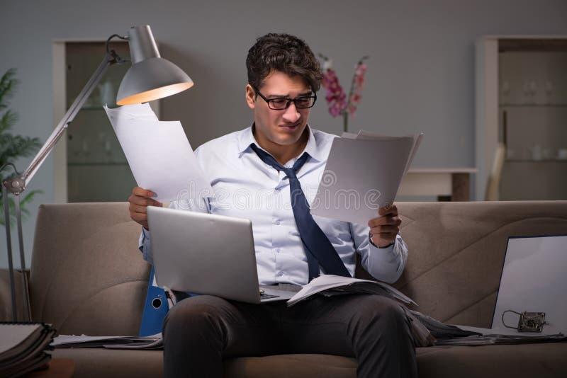 Le bourreau de travail d'homme d'affaires fonctionnant tard à la maison photo stock