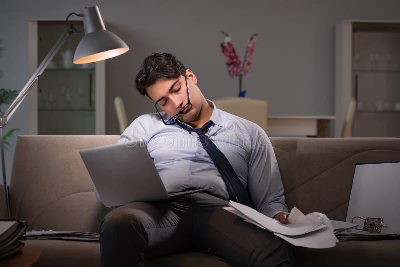 Le bourreau de travail d'homme d'affaires fonctionnant tard à la maison image stock