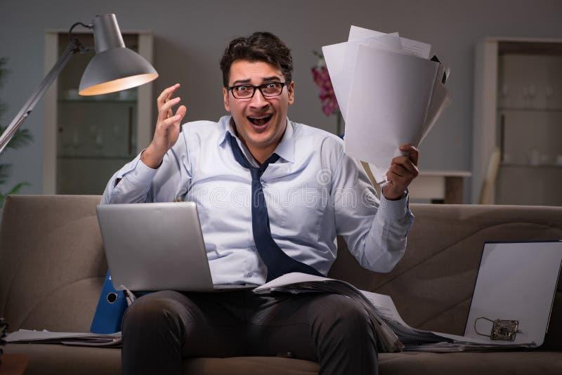Le bourreau de travail d'homme d'affaires fonctionnant tard à la maison images stock