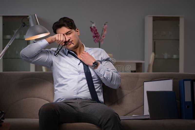Le bourreau de travail d'homme d'affaires fonctionnant tard à la maison photographie stock