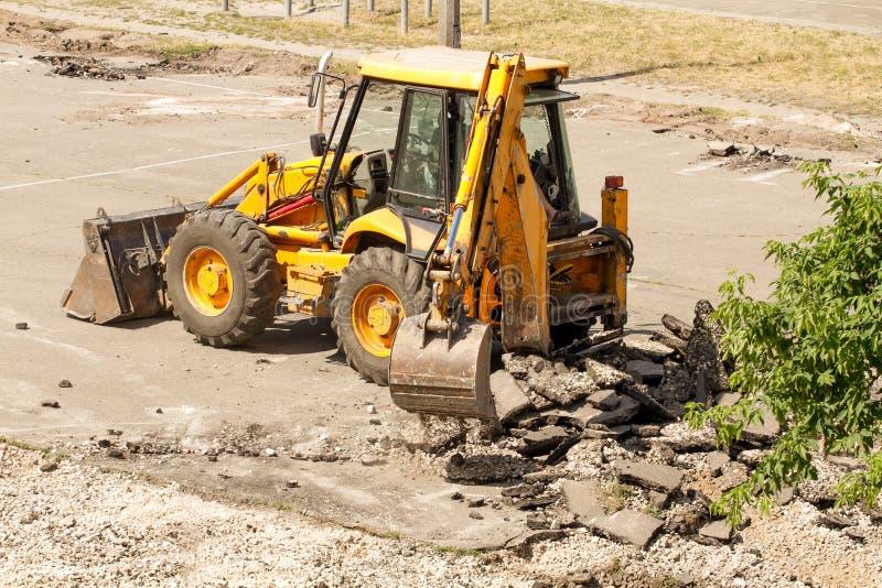 Le bouteur démantèle l'asphalte au travail image stock