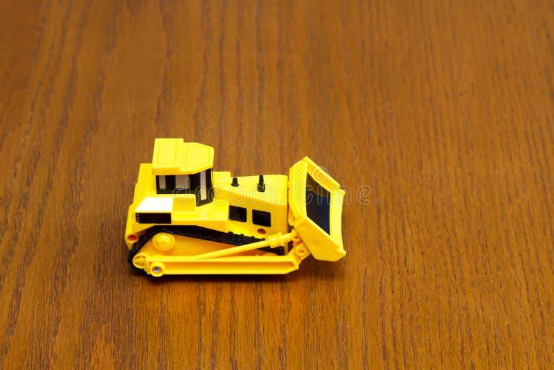 Le bouteur joue avec des roues faites de plastique sur un fond en bois de texture de grain photographie stock libre de droits