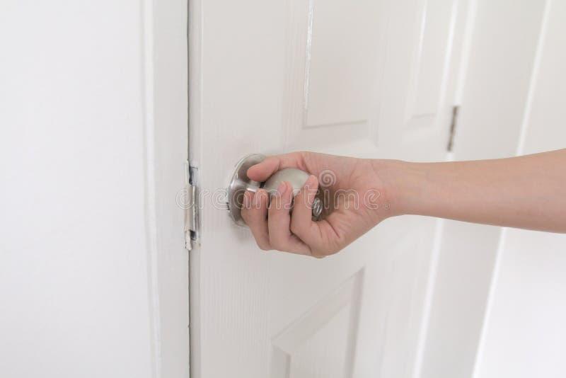Le bouton de porte inoxydable de poignée en gros plan de jeune femme, femmes sont porte d'ouverture, se ferment vers le haut du b photos libres de droits