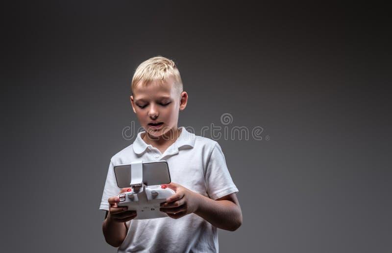 Le boxeur beau de petit garçon avec les cheveux blonds habillés dans un T-shirt blanc juge un contrôle de quadcopter à distance images stock