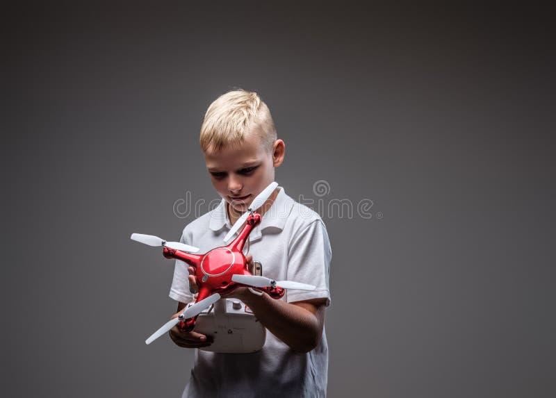 Le boxeur beau de petit garçon avec les cheveux blonds habillés dans un T-shirt blanc tient un extérieur de quadcopter et de cont photo stock