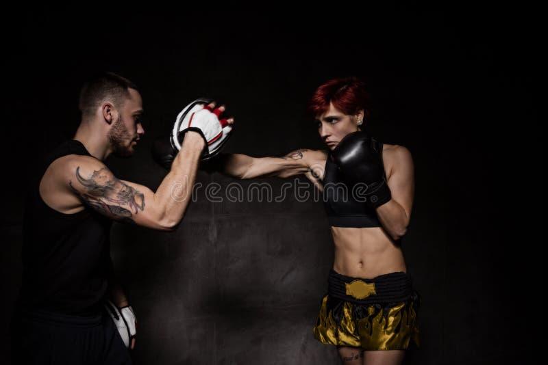 Le boxeur de femme frappant des gants de formation a tenu un entraîneur de boxe photo libre de droits