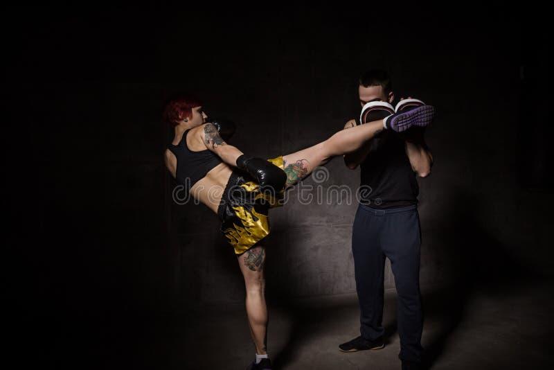 Le boxeur de femme frappant des gants de formation a tenu un entraîneur de boxe images stock