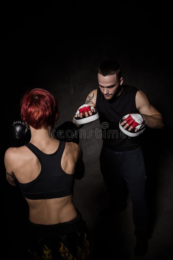 Le boxeur de femme frappant des gants de formation a tenu un entraîneur de boxe photo stock