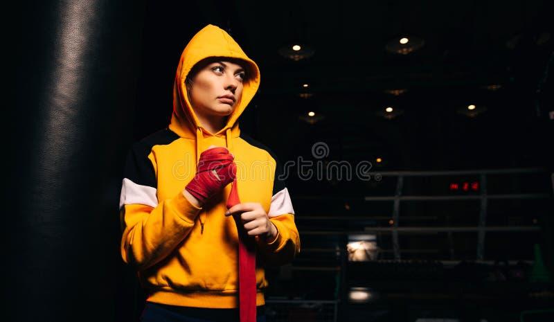Le boxeur de fille de sports dans le pull molletonné jaune tire les bandages rouges sur ses mains image libre de droits