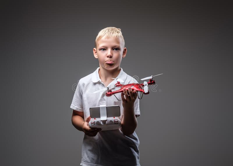 Le boxeur drôle de garçon avec les cheveux blonds habillés dans un T-shirt blanc tient un extérieur de quadcopter et de contrôle image libre de droits