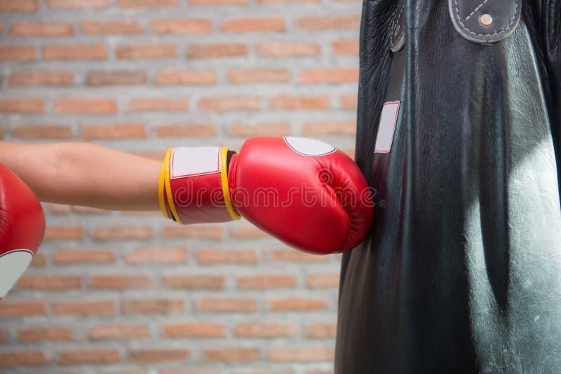 Le boxeur poinçonne un sac de sable photographie stock