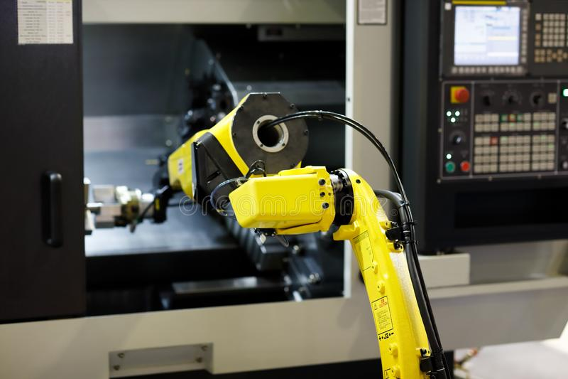 Le bras de robot charge le détail dans la machine de tour de commande numérique par ordinateur image stock
