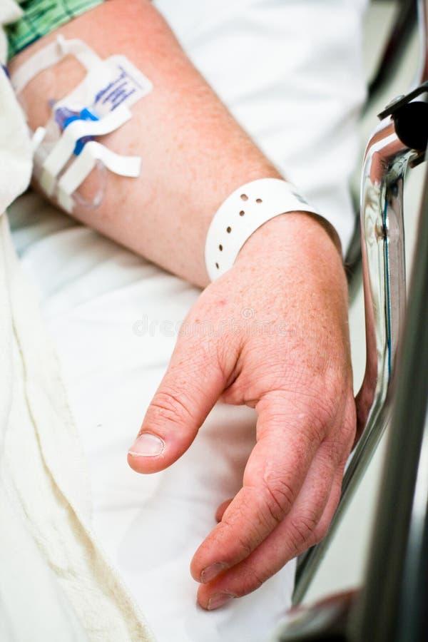 Le bras du patient hospitalisé avec le wristband et IV images libres de droits