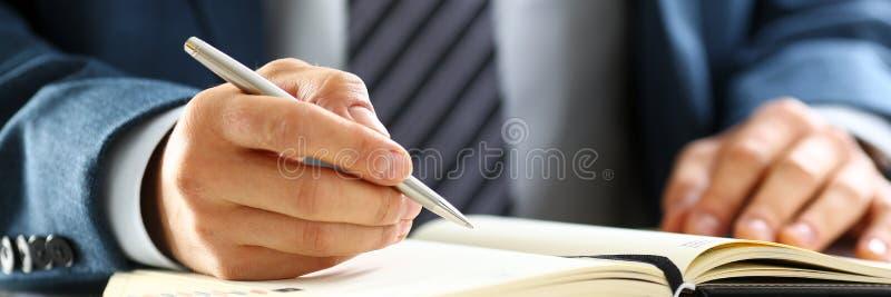 Le bras masculin dans le costume et le lien tiennent le stylo argenté photo libre de droits