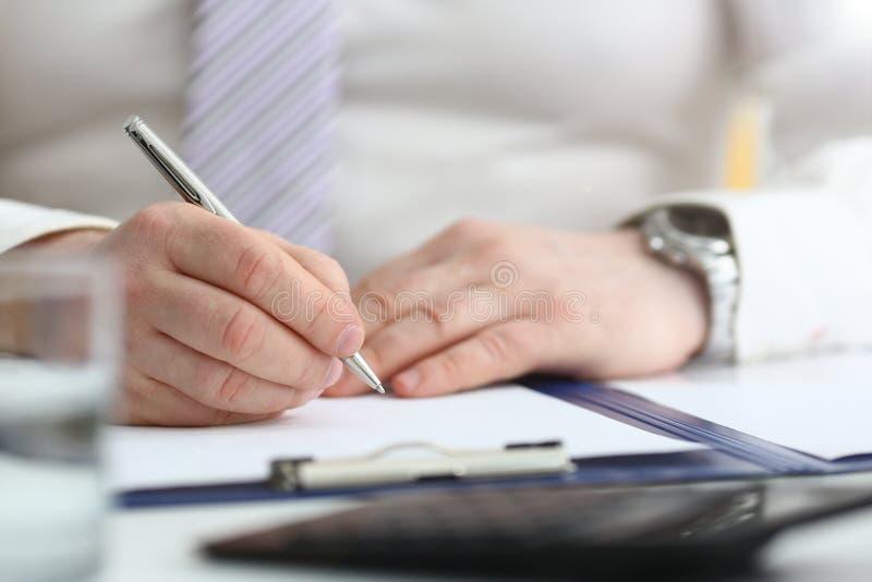 Le bras masculin dans le costume et le lien tiennent le stylo argent? images libres de droits