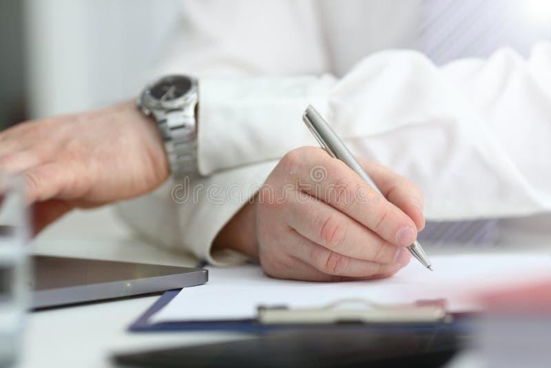 Le bras masculin dans le costume et le lien tiennent le stylo argent? images stock