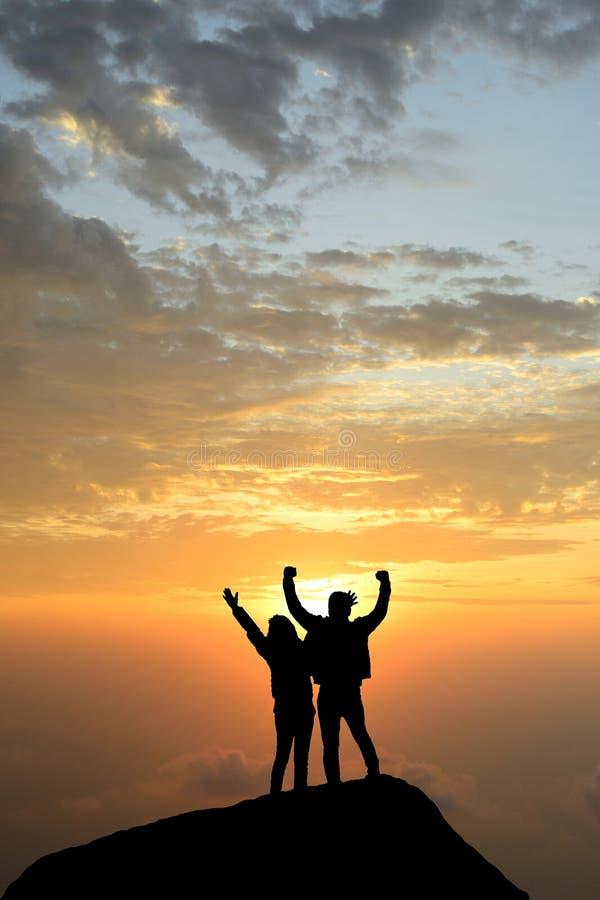 Le bras réussi d'accomplissements de silhouette vers le haut des couples est sur la crête de h photos stock