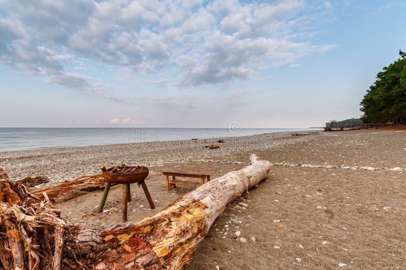 Le brasero en métal, le tronc d'un arbre tombé et un banc sont support sur le rivage abandonné d'une mer calme une soirée d'été images stock
