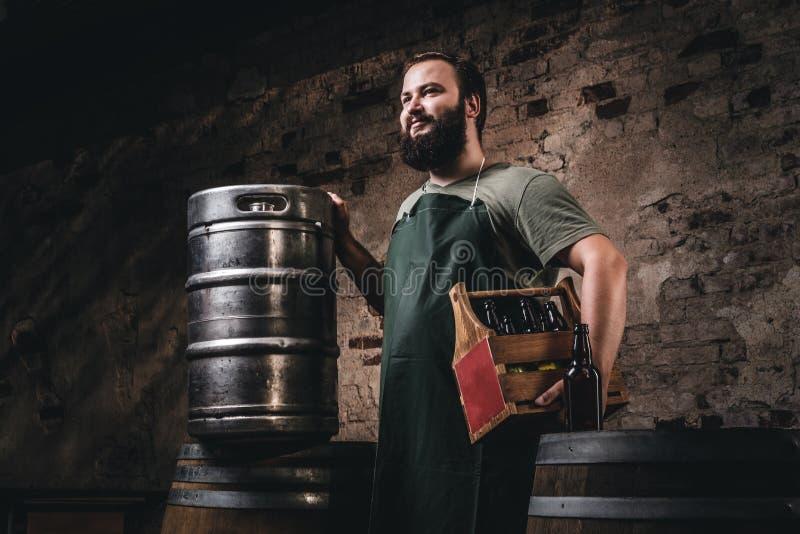 Le brasseur barbu dans le tablier tient la boîte en bois avec de la bière tout en tenant les barils proches à l'usine de brasseri photographie stock libre de droits