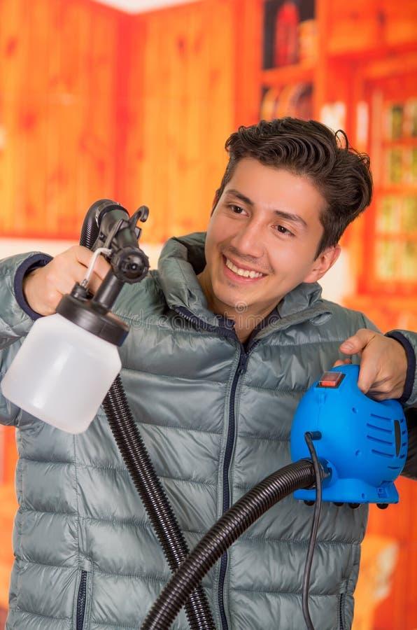 Le bricoleur de sourire beau se tenant dans le sien remet le pistolet de pulvérisation de peinture, utiliser une veste grise à un photographie stock