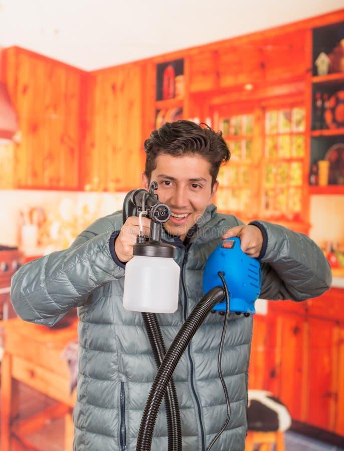 Le bricoleur de sourire beau se tenant dans le sien remet le pistolet de pulvérisation de peinture, utiliser une veste grise à un photographie stock libre de droits