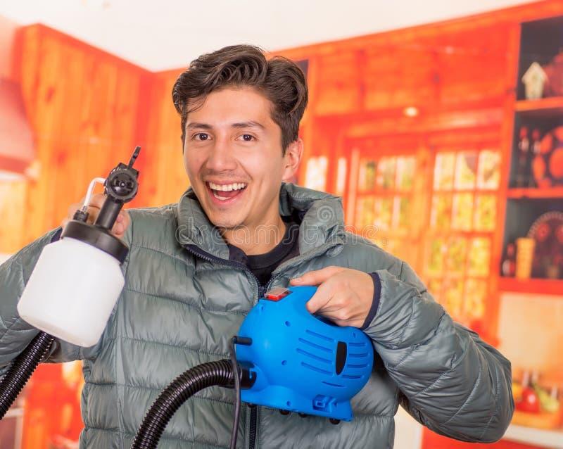 Le bricoleur de sourire beau se tenant dans le sien remet le pistolet de pulvérisation de peinture, utiliser une veste grise à un photo libre de droits