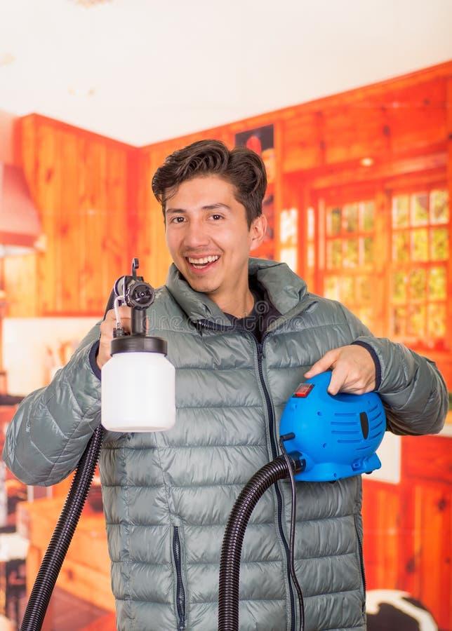 Le bricoleur de sourire beau se tenant dans le sien remet le pistolet de pulvérisation de peinture, utiliser une veste grise à un photos stock