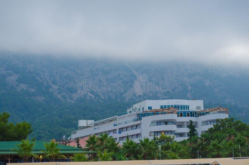 Le brouillard descend des montagnes à un bâtiment résidentiel photographie stock libre de droits