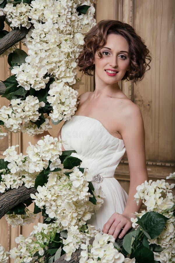 Le bruden som omges av vita blommor arkivfoton