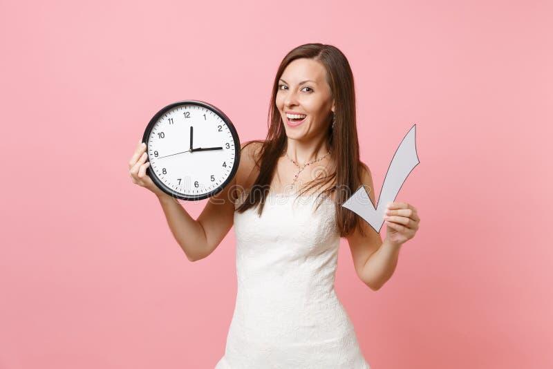 Le brudkvinnan snöra åt in fläcken för bröllopsklänninginnehavkontrollen och den runda ringklockan på pastellfärgad rosa bakgrund royaltyfri foto