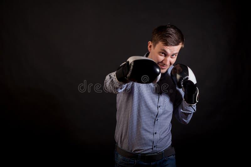 Le brun dans une chemise de plaid avec des gants de boxe sur ses mains poignarde image libre de droits