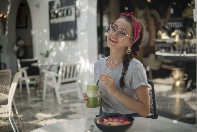 Le brunettflickan i en röd bandana och med flätan som har en tropisk lunch i öppet kafé, grön coctail och bunke med royaltyfri bild