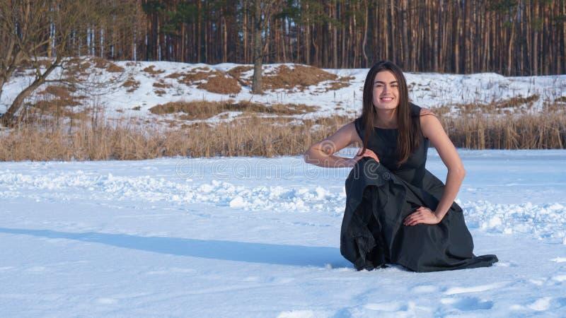Le brunettflickan i en svart klänning i en snöig skog royaltyfri bild