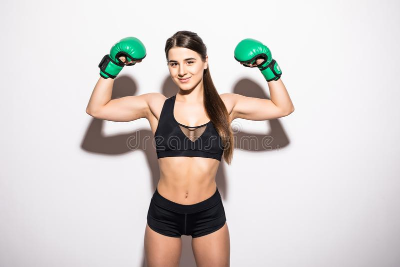 Le brunettkonditionkvinnan i boxninghandskar som visar henne biceps, medan se kameran över vit bakgrund royaltyfria foton