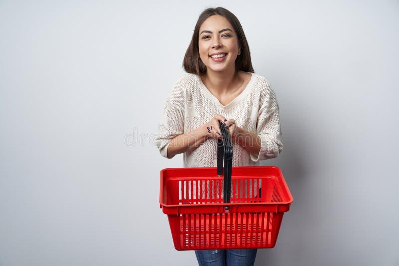 Le brunettkvinnaanseende av den vita väggen som rymmer den tomma shoppa korgen royaltyfri fotografi