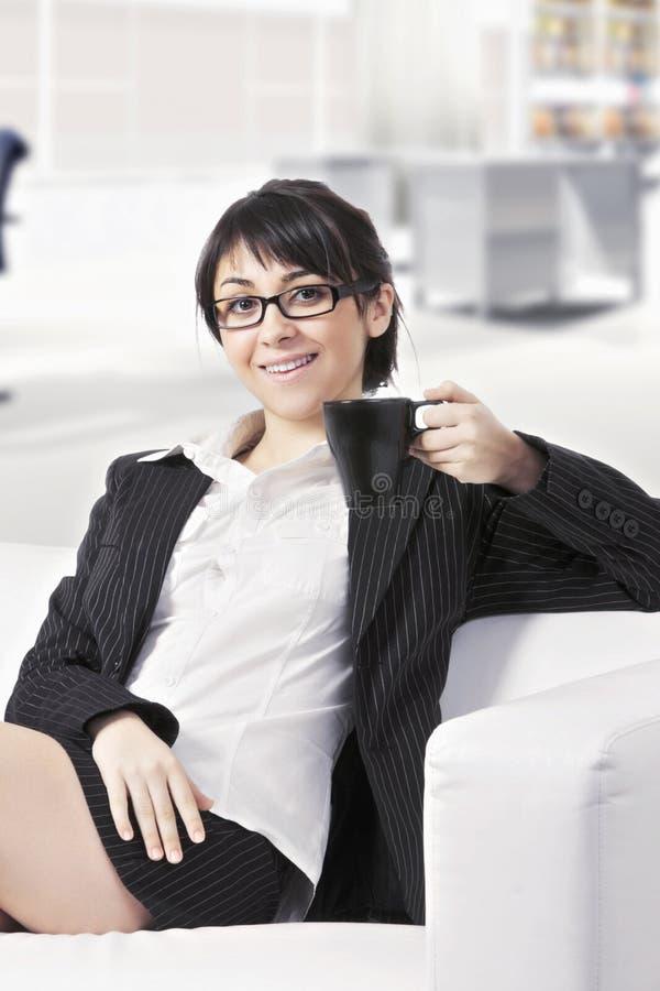 Le brunettkvinnan på soffan på kontoret arkivbilder