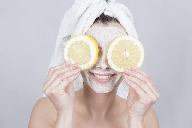 Le brunettkvinnan som rymmer skiva två av citronen främst av hennes framsida kvinna med att fukta den ansikts- maskeringen arkivbilder