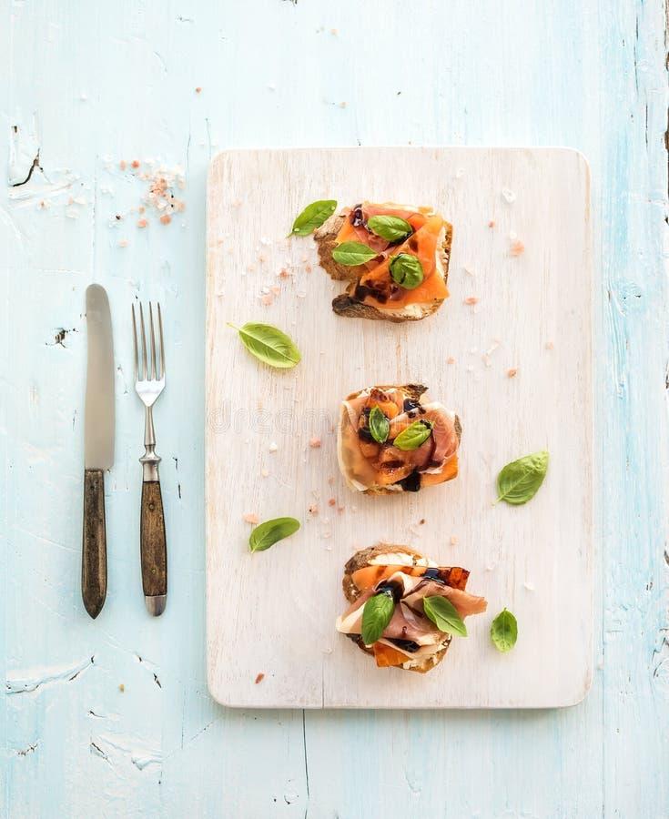 Le Bruschette con il prosciutto di Parma, il melone arrostito, il formaggio a pasta molle ed il basilico sul servizio di legno im fotografia stock