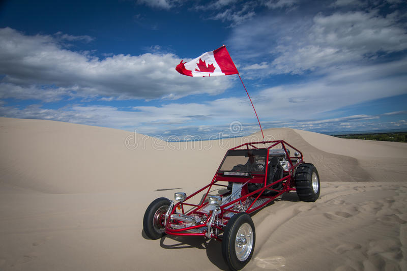 Le buggy des sables rouge brillant de sable s'est garé dans le sable photos stock