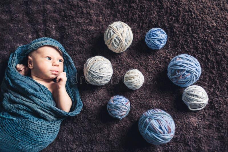 Le bugie del neonato avvolte in coperta in mezzo dei grovigli del filo e distoglie lo sguardo fotografie stock