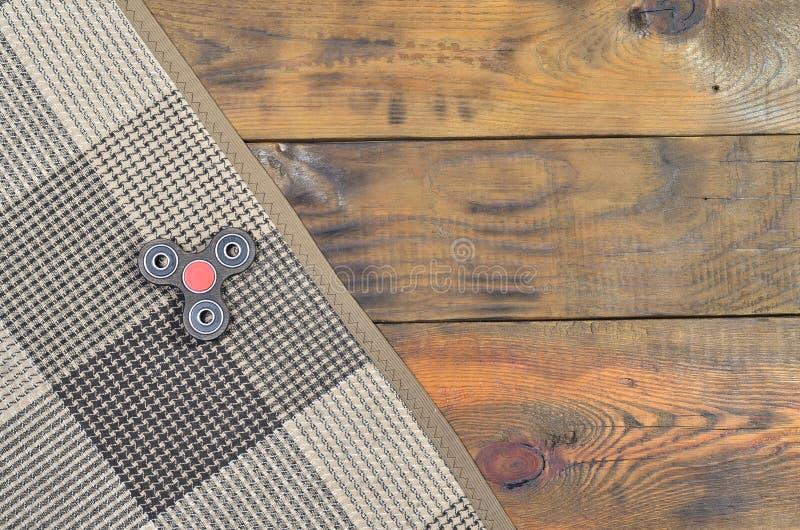 Le bugie fatte a mano di legno rare di un filatore su un plaid a quadretti su un fondo di legno marrone sorgono Alleviamento di s fotografie stock libere da diritti