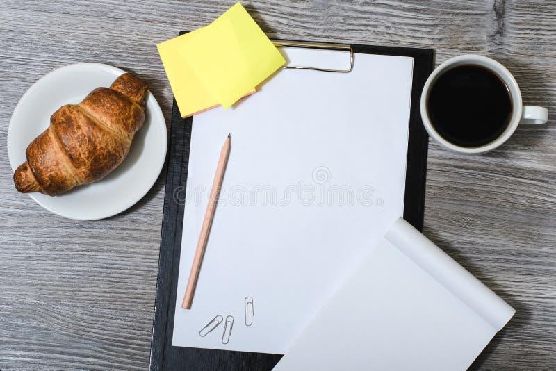 Le bureau accessoirisent sur la table grise en bois : presse-papiers, tasse de coffe images stock