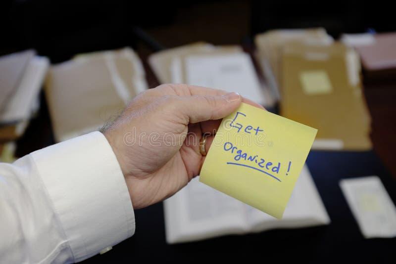 Le bureau avec la main de dossiers tenant dire d'autocollant obtiennent organisé images libres de droits