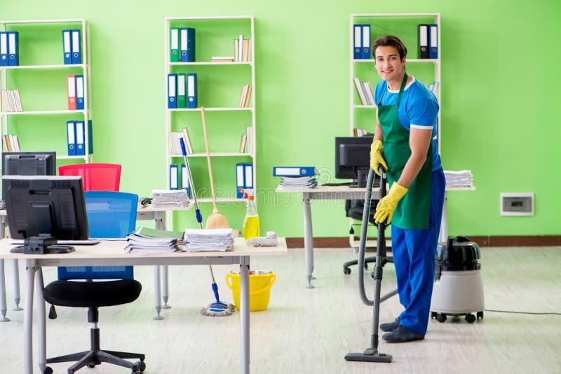Le bureau beau de nettoyage d'homme avec l'aspirateur images libres de droits
