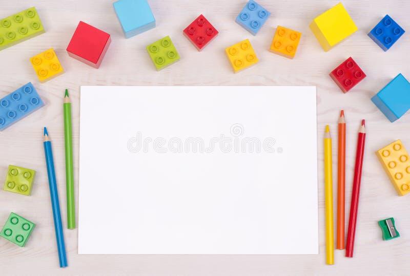 Le bureau de l'enfant avec les blocs constitutifs colorés et les crayons, vue supérieure avec l'espace de copie image libre de droits
