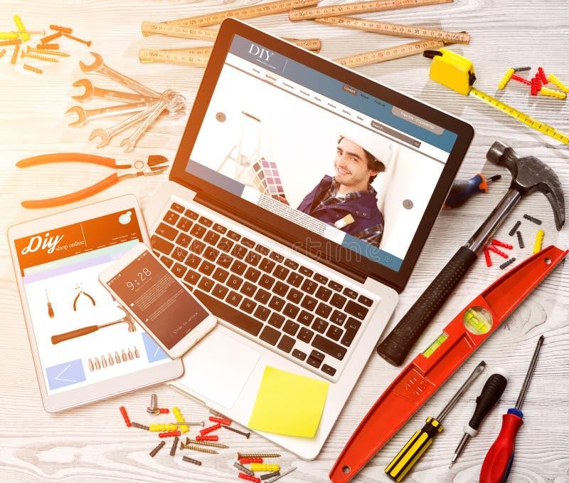 Le bureau du bricoleur en bois dans la définition élevée avec l'ordinateur portable, comprimé et image libre de droits
